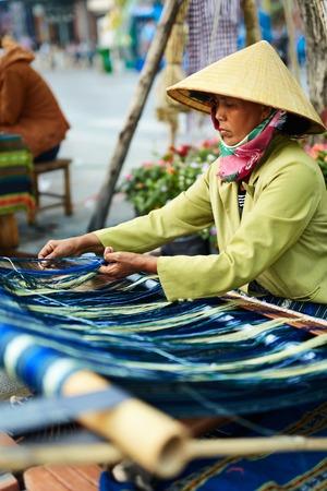 non la: VIETNAM, HO CHI MINH - FEBRUARY 6, 2016: Portrait Of Vietnamese Woman In Traditional Conical Hat, Non La Weaving Yarn On Street. Female Textile Weaver Preparing Warp On Hand Backstrap Loom Outdoors