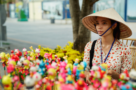 non la: VIETNAM, HO CHI MINH - FEBRUARY 6, 2016: Closeup Portrait Of Beautiful Vietnamese Woman Merchant Wearing National Traditional Conical Hat, Non La Selling Souvenirs At Local Street Market