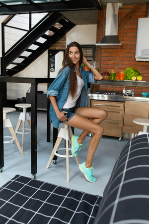 beautiful model: Healthy Fit Woman Lifestyle. Girl Sitting In Kitchen With Fresh Vegetable Juice, Detox Smoothies And Fruits On Table. Beautiful Model Prefers To Eat Fitness Food, Weight Loss Drinks. Nutrition Concept