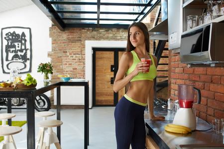 tomando jugo: Detox dieta Smoothie de la bebida. Mujer sana con el cuerpo en forma orgánica que bebe el zumo fresco en la cocina. Hermosa feliz sonriente de la muchacha modelo en Ejercicios de deporte que gozan del alimento de pérdida de peso. Concepto de nutrición