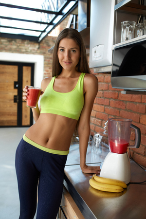 cleanse: Detox Smoothie Diet Drink. Healthy Woman With Fit Body Drinking Fresh Organic Juice In Kitchen. Beautiful Happy Smiling Girl Model In Fitness Sportswear Enjoying Weight Loss Food. Nutrition Concept Stock Photo
