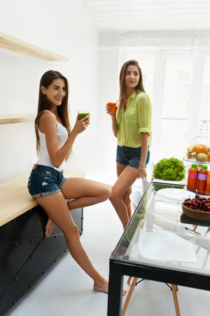 ni�as gemelas: Detox Juice For Healthy Nutrition. Beautiful Happy Smiling Women Drinking Fresh Vegetable Detox Juice Smoothie Home. Twin Girls Enjoying Vegan Weight Loss Drink In Dining Room. Fitness Diet Concept
