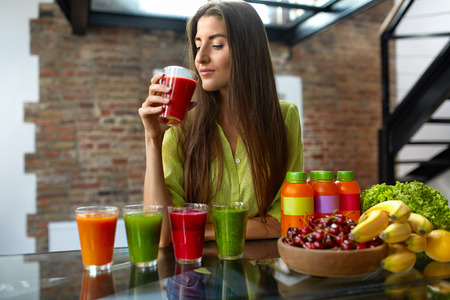 Fitness Food. Healthy Eating Woman On Diet Drinking Fresh Detox Juice, Smoothie For Breakfast. Closeup Of Beautiful Smiling Girl With Fruits And Weight Loss Drinks At Kitchen Table. Nutrition Concept Stock Photo