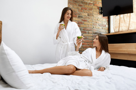 cleanse: Detox Diet. Healthy Women Drinking Water After Waking Up In Morning. Beautiful Twins Girls In Bathrobes With Vitamin-Fortified Organic Lemon, Mint Drink Indoors. Cleanse Dieting, Weight Loss Nutrition Stock Photo