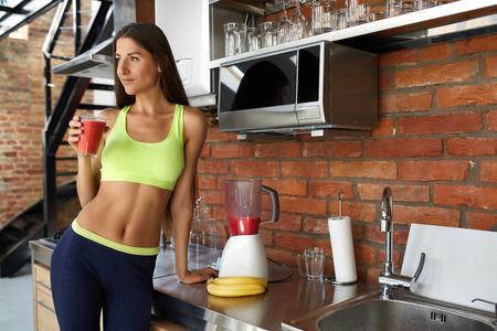 Detox dieta Smoothie de la bebida. Mujer sana con el cuerpo en forma orgánica que bebe el zumo fresco en la cocina. Hermosa feliz sonriente de la muchacha modelo en Ejercicios de deporte que gozan del alimento de pérdida de peso. Concepto de nutrición