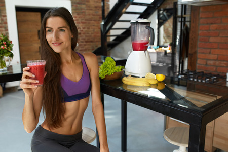 sexy food: Detox Diet For Healthy Eating Woman. Fitness Female Model With Fit Body Drinking Fresh Smoothie Juice In Kitchen. Beautiful Smiling Girl In Sexy Sportswear Enjoying Weight Loss Food. Nutrition Concept