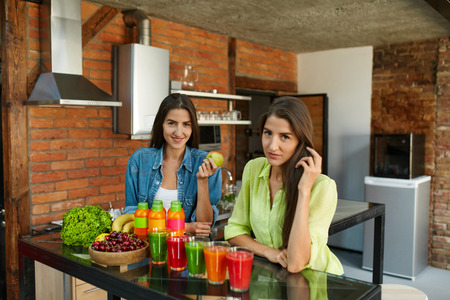 cleanse: Diet Nutrition With Detox Juice. Healthy Women Posing Near Table With Glasses Of Fresh Juice, Bottles Of Green Detox Smoothie And Fruits On It. Closeup Of Happy Beautiful Fit Girls Smiling In Kitchen