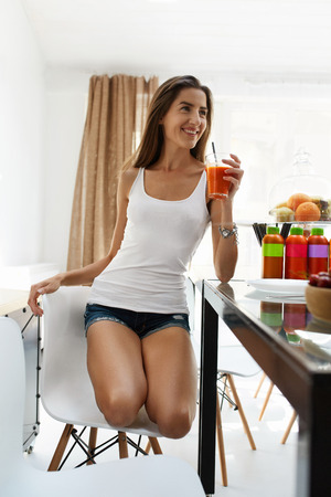 cleanse: Healthy Diet For Woman. Happy Smiling Girl Drinking Fresh Vegetable Detox Juice Smoothie Home. Beautiful Female Model Relaxing In Dining Room With Glass Of Vegan Weight Loss Drink. Fitness Nutrition