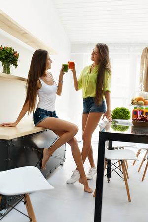 niñas gemelas: Jugo de desintoxicación para una nutrición sana. Hermosas mujeres felices de consumición sonriente de desintoxicación jugo de las verduras frescas Smoothie Inicio. Gemelas chicas disfrutando vegano pérdida de peso de la bebida en comedor. Concepto de la dieta de la aptitud