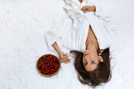 cleanse: Healthy Diet Food For Womans Health. Closeup Portrait Of Beautiful Happy Woman Eating Organic Cherries. Smiling Vegan Girl In Bathrobe Relaxing On Bed In Morning. Fitness Food, Weight Loss Nutrition