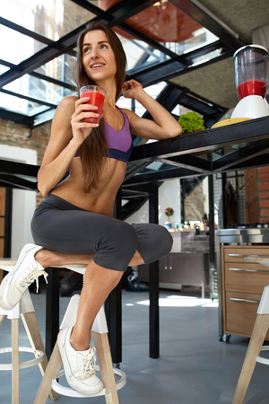 cleanse: Fitness Food. Healthy Eating Woman With Fit Body Drinking Fresh Smoothie Juice In Kitchen. Beautiful Smiling Model Girl In Sexy Sportswear Enjoying Cleanse Detox Diet. Weight Loss Nutrition Concept