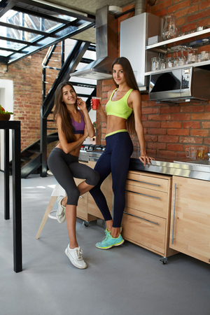 ropa deportiva: Healthy Nutrition And Fitness. Fit Sport Women In Sexy Fashion Sportswear Drinking Fresh Organic Juice, Smoothie Drink At Home Before Workout Indoors. Beautiful Smiling Girls On Detox Weight Loss Diet