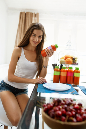 cleanse: Healthy Food And Nutrition Concept. Woman On Diet Having Detox Juice For A Meal. Happy Beautiful Girl Drinking Fresh Vegan Smoothie At Home, Fruits And Bottles With Dieting Weight Loss Drink On Table Stock Photo
