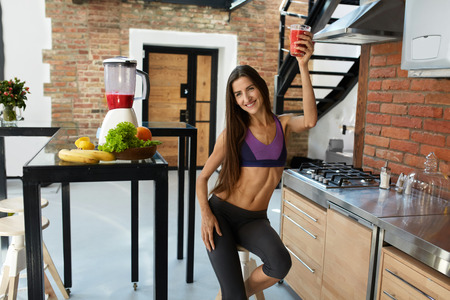 woman smiling: Fitness Food. Healthy Eating Woman With Fit Body Drinking Fresh Smoothie Juice In Kitchen. Beautiful Smiling Model Girl In Sexy Sportswear Enjoying Cleanse Detox Diet. Weight Loss Nutrition Concept