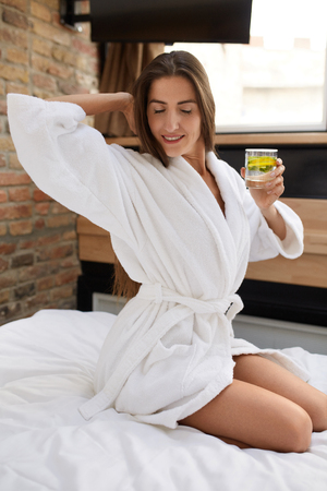 cleanse: Detox Diet. Healthy Woman Drinking Water After Waking Up In Morning. Beautiful Happy Girl Holding Fresh Vitamin-Fortified Water Flavored With Organic Lemon Mint. Cleanse Dieting, Weight Loss Nutrition Stock Photo