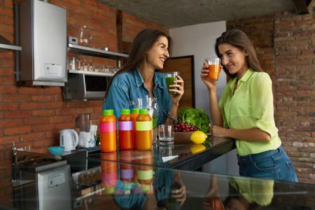 tomando jugo: Weight Loss Diet. Healthy Eating Women Drinking Fresh Detox Juice, Green Smoothie In Kitchen. Beautiful Happy Fit Girls Enjoying Vegetable Drinks, Bottles Standing On Table. Fitness Nutrition Concept