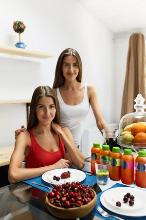 Diet Nutrition With Detox Juice. Healthy Women Posing Near Table With Glasses Of Fresh Juice, Bottles Of Green Detox Smoothie And Fruits On It. Closeup Of Happy Beautiful Fit Girls Smiling In Kitchen