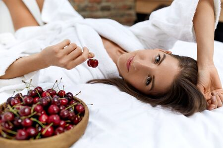 beauty body: Healthy Diet Food For Womans Health. Closeup Portrait Of Beautiful Happy Woman Eating Organic Cherries. Smiling Vegan Girl In Bathrobe Relaxing On Bed In Morning. Fitness Food, Weight Loss Nutrition