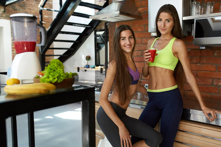 sisters sexy: Healthy Nutrition And Fitness. Fit Sport Women In Sexy Fashion Sportswear Drinking Fresh Organic Juice, Smoothie Drink At Home Before Workout Indoors. Beautiful Smiling Girls On Detox Weight Loss Diet