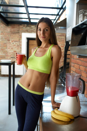 fit: Detox Smoothie Diet Drink. Healthy Woman With Fit Body Drinking Fresh Organic Juice In Kitchen. Beautiful Happy Smiling Girl Model In Fitness Sportswear Enjoying Weight Loss Food. Nutrition Concept Stock Photo
