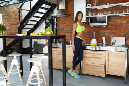Healthy Nutrition. Fit Woman On A Diet Making Detox Smoothie Juice In Kitchen. Beautiful Happy Smiling Vegan Girl In Fitness Sportswear Preparing Fresh Organic Drink. Weight Loss Dieting Food Concept Stock Photo