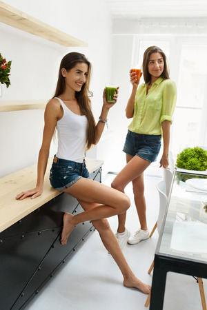 Detox Juice For Healthy Nutrition. Beautiful Happy Smiling Women Drinking Fresh Vegetable Detox Juice Smoothie Home. Twin Girls Enjoying Vegan Weight Loss Drink In Dining Room. Fitness Diet Concept