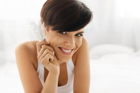 Krása Péče o pleť. Detailním portrét krásné šťastné mladá žena s dokonalou Soft kůže a přírodní make-up se jí dotýkat čistý čerstvým tvář s bílé pírko. Zdravé Usmívající se žena relaxaci Indoors Reklamní fotografie