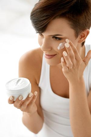 뷰티 스킨 케어. 아름다운 행복한 여자 청소 얼굴에 화장품 크림을 적용합니다. 건강한 자연 메이크업 여성 모델 미소의 근접 촬영 초상화, 신선한 소 스톡 콘텐츠