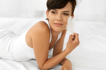 Krásná usmívající se žena s novou tvář dotýkal její jemnou kůží S bílé pírko ležící na posteli. Detailním Portrét zdravých šťastná dívka s přirozeným make-up pro mladé v interiéru. Krása, péče o pleť Concept