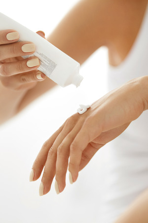 Hand Skin Care. Close Up Of Female Hands Holding Cream Tube, Beautiful Woman Hands With Natural Manicure Nails Applying Cosmetic Hand Cream On Soft Silky Healthy Skin. Beauty And Body Care Concept Stock Photo