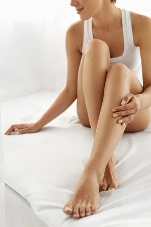 pies sexis: Depilación Concepto. Primer de la mano de la mujer hermosa con manicura natural Tocar Piernas largas atractivas. Mujer joven que toca su piel suave y sedosa sin pelo perfecto. Concepto Cuidado del cuerpo Belleza