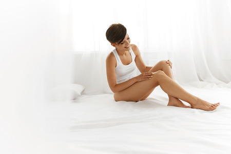 female legs: Beauty Body Woman. Beautiful Happy Smiling Girl Touching Sexy Epilated Long Legs On White Bed. Female Enjoying Perfect Hairless Smooth Soft Skin Indoors. Hair Removal, Depilation And Epilation Concept Stock Photo