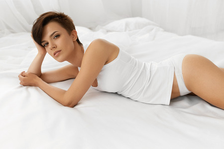 Woman Beauty. Beautiful Sexy Young Woman With Natural Makeup Lying On White Bed. Healthy Female Model With Fresh Soft Face Skin Relaxing Indoors. Body Care, Women Health Concept