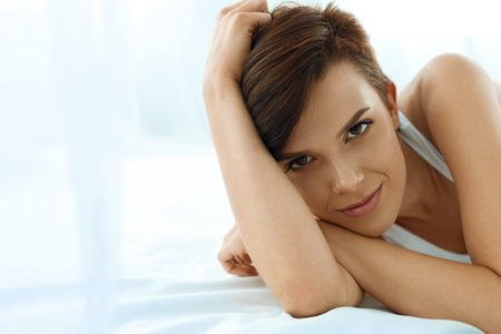 beauty skin: Womans Health. Closeup Portrait Of Beautiful Smiling Woman With Fresh Face, Soft Skin Having Fun Lying On White Bed. Healthy Happy Girl With Natural Makeup Relaxing Indoors. Beauty, Skin Care Concept Stock Photo