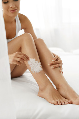 female legs: Woman Body Care. Beautiful Happy Healthy Smiling Girl Touching Sexy Slender Long Legs With White Feather. Female Enjoying Perfect Hairless Smooth Soft Skin On White Bed. Epilation, Beauty Concepts