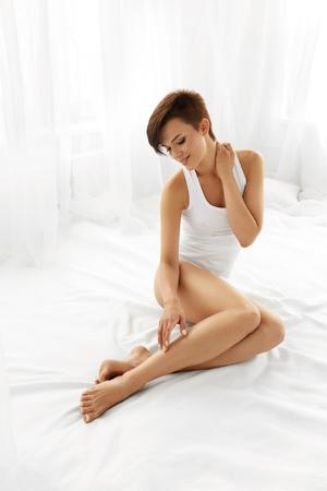 Žena Péče o tělo. Krásná šťastný zdravým dívky dotýká sexy dlouhé nohy. Žena se těší Perfektní naháč hladká měkká a hedvábná pleť sedící na bílé posteli. Krása, Depilace Epilace A Concept Reklamní fotografie