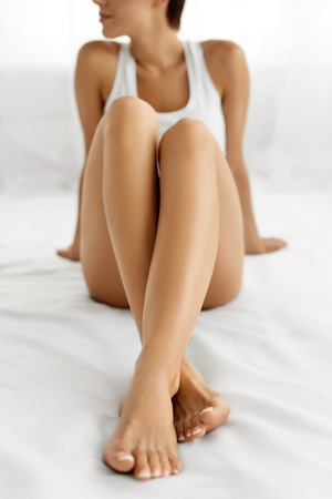 Woman Body Care. Closeup Of Beautiful Happy Girl With Sexy Slender Long Legs And Perfect Hairless Healthy Smooth Soft Skin Sitting On White Bed. Health And Beauty Concept