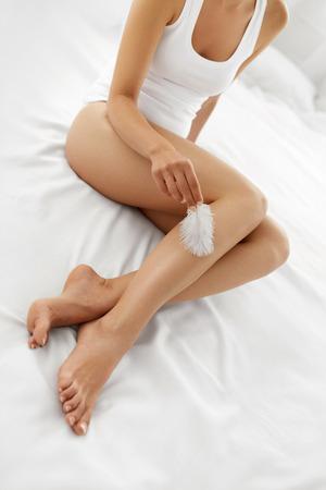 Schöne weiche Haut. Nahaufnahme Der Lange Frau Beine mit perfekten Hairless glatte und seidige Haut, Hand der Frau touhing ihren sexy schlanke Beine mit weißer Feder. Haarentfernung, Schönheit, Körperpflege, Konzepte Standard-Bild