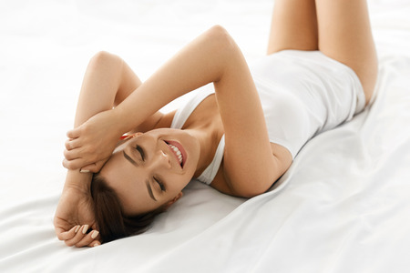 female beauty: Beauty And Health. Beautiful Smiling Woman With Fresh Soft Skin And Natural Makeup In Underwear Having Fun Lying On White Bed. Healthy Happy Female Model Relaxing Indoors. Body And Skin Care Concept