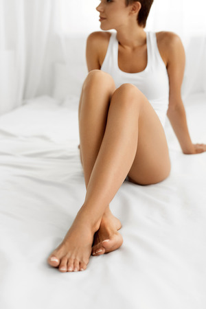 hairless: Woman Body Care. Closeup Of Beautiful Happy Girl With Sexy Slender Long Legs And Perfect Hairless Healthy Smooth Soft Skin Sitting On White Bed. Health And Beauty Concept