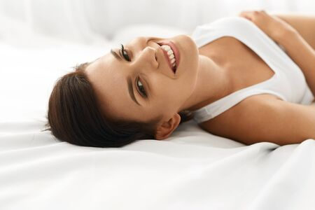 woman lying: Womans Health. Closeup Portrait Of Beautiful Smiling Woman With Fresh Face, Soft Skin Having Fun Lying On White Bed. Healthy Happy Girl With Natural Makeup Relaxing Indoors. Beauty, Skin Care Concept Stock Photo