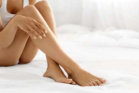 sexy young girl: Удаление волос Concept. Макрофотография рука красивая женщина с естественной Маникюр Прикосновение Sexy длинные ноги. Молодая женщина, касаясь ее идеальный голая Smooth мягкой и шелковистой кожи. Красота Body Care Concept