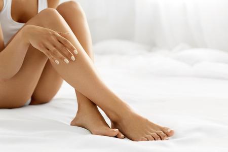 Depilace Concept. Detailní záběr z rukou krásné ženy se s přirozeným Manikúra Dotyk sexy dlouhé nohy. Mladá žena se jí dotýkat Perfektní bezsrsté Smooth měkká a hedvábná pleť. Krása Concept Péče o tělo