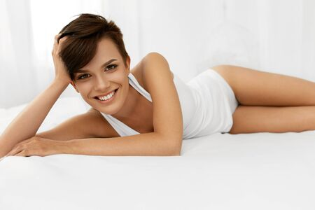 woman underwear: Beauty And Health. Beautiful Smiling Woman With Fresh Soft Skin And Natural Makeup In Underwear Having Fun Lying On White Bed. Healthy Happy Female Model Relaxing Indoors. Body And Skin Care Concept