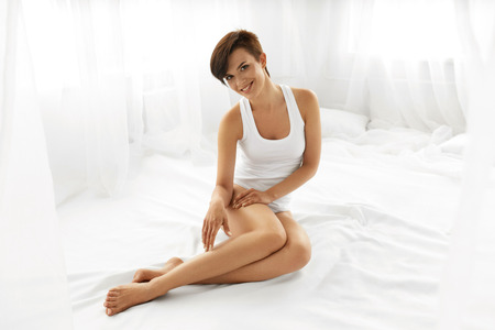 hairless: Beauty Body Woman. Beautiful Happy Smiling Girl Touching Sexy Epilated Long Legs On White Bed. Female Enjoying Perfect Hairless Smooth Soft Skin Indoors. Hair Removal, Depilation And Epilation Concept Stock Photo
