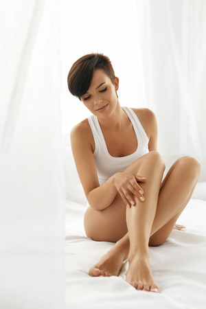 Woman Body Care. Beautiful Happy Healthy Girl Touching Sexy Long Legs. Female Enjoying Perfect Hairless Smooth Soft And Silky Skin Sitting On White Bed. Beauty, Hair Removal And Epilation Concept