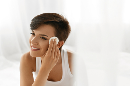 model face: Beauty Skin Care. Beautiful Happy Woman Removing Face Makeup Using Cotton Pad. Closeup Portrait Of Healthy Smiling Female Model With Natural Makeup Touching Perfect Fresh Soft Skin, Cleaning Her Face