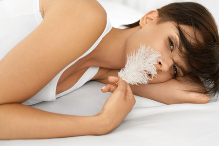 silky hair: Beautiful Smiling Woman With Fresh Face Touching Her Soft Skin With White Feather Lying On Bed. Closeup Portrait Of Healthy Happy Girl With Natural Makeup Relaxing Indoors. Beauty, Skin Care Concept
