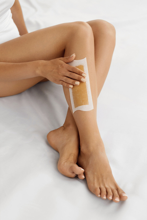 Body Care. Long Womans Legs With Wax Strip On. Beautiful Female Depilates Her Sexy Slender Long Legs By Waxing For Perfect Hairless Smooth And Silky Skin. Epilation Hair Removal, Beauty Concept