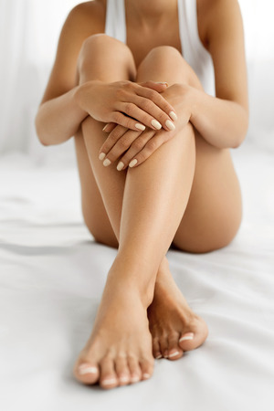 footcare: Woman Body Care. Close Up Of Long Female Legs With Perfect Smooth Soft Skin, Pedicure And Beautiful Hands With Natural Manicure, Healthy Nails On White Bed. Epilation, Beauty And Health Concepts